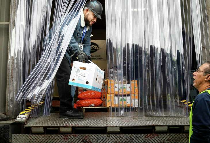 "Robert Alcocer, left, who works in receiving for Brothers Produce, helps Eddie Gonzalez load food into a delivery van on Thursday, Nov. 21, 2019, in Houston. Gonzalez, who retired from the Army after 21 years, works for Second Servings. It is a non-profit organization that takes surplus food from businesses and distributes it to charities. ""I always wanted to help the needy,"" Gonzalez said. Brothers Produce donated two truckloads of food to help area charities affected by the ammonia leak at the Houston Food Bank."