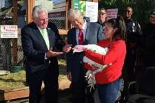 Norwalk Mayor Harry Rilling joins Stew Leonard Sr. to pardon Sonnie the turkey with the help of employee Evelin Jaimes as Stew Leonard's Turkey Brigade hands out Thanksgiving turkeys to residents in need, soup kitchen reps, homeless shelters and other charities via human assembly line Thursday, November 21, 2019, at the store in Norwalk, Conn. Over 3,000 turkeys were distributed as part of the 4oth annual event.