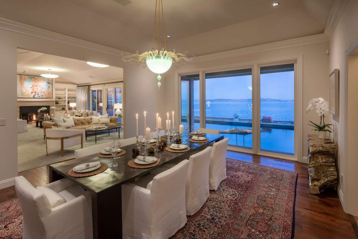 A formal dining room has large windows featuring Bay views.