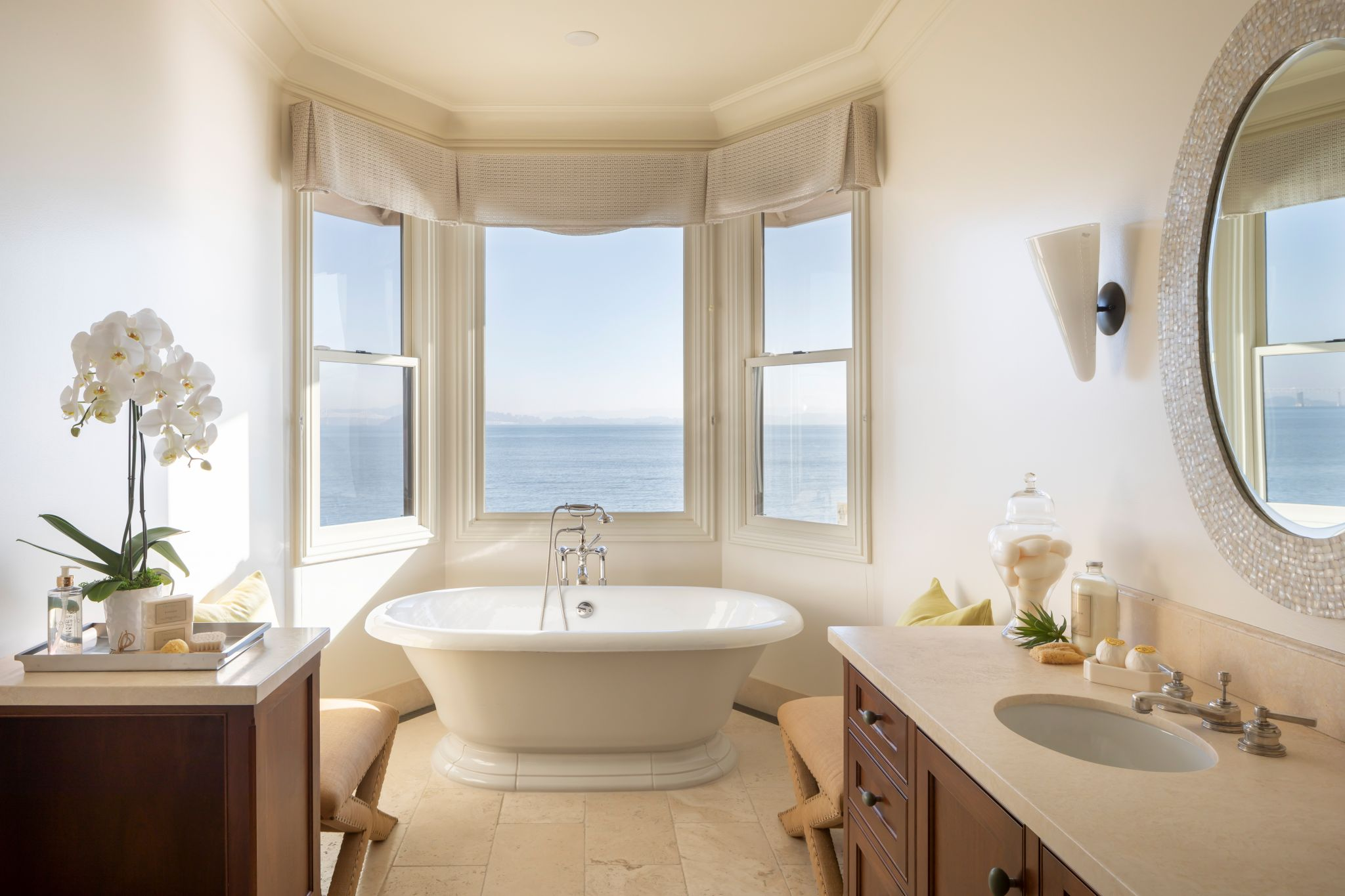 The primary bathroom includes a bathtub that is framed by windows overlooking the water.