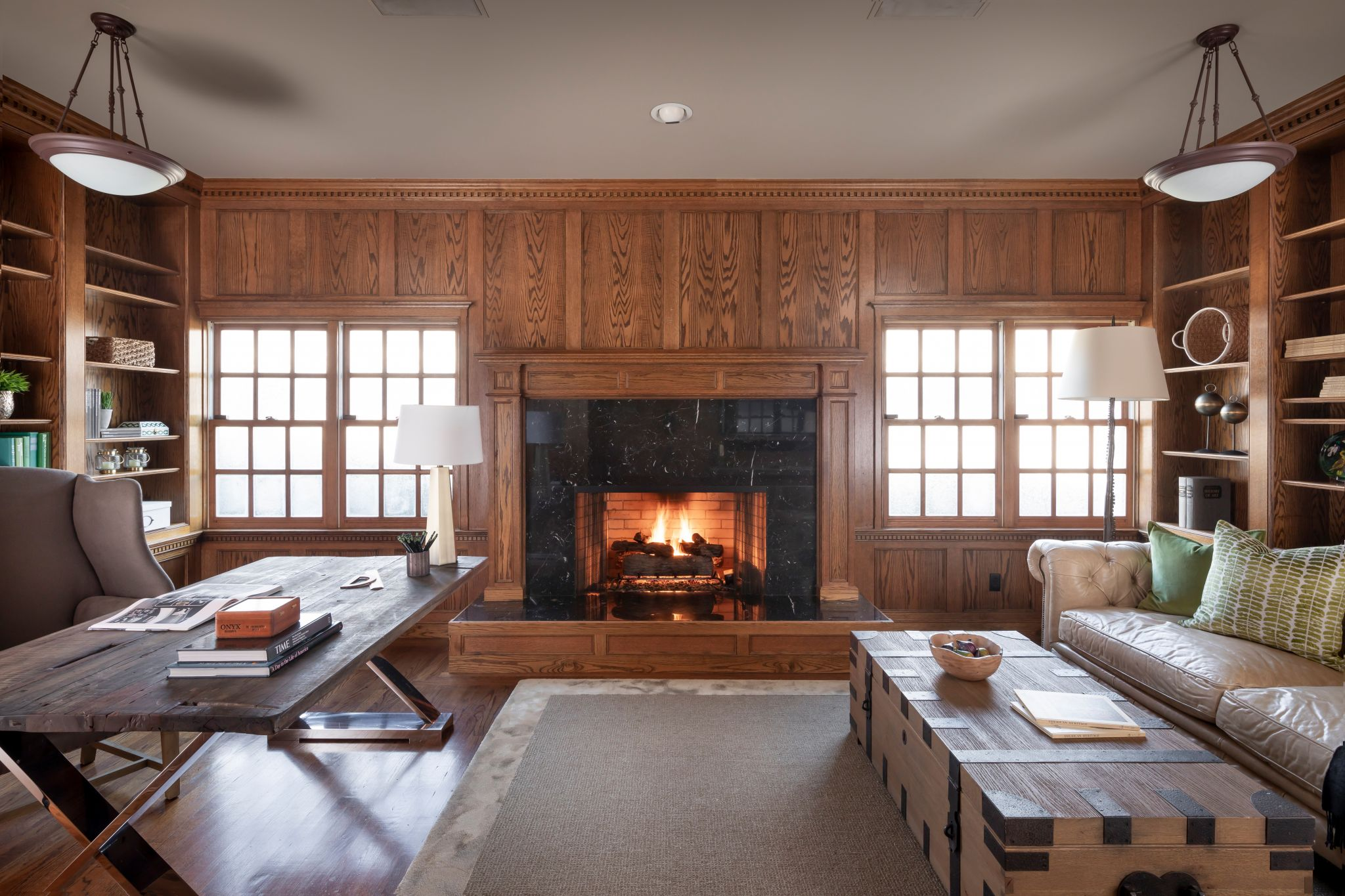 A cozy study is paneled in natural wood with a fireplace as its focal point.
