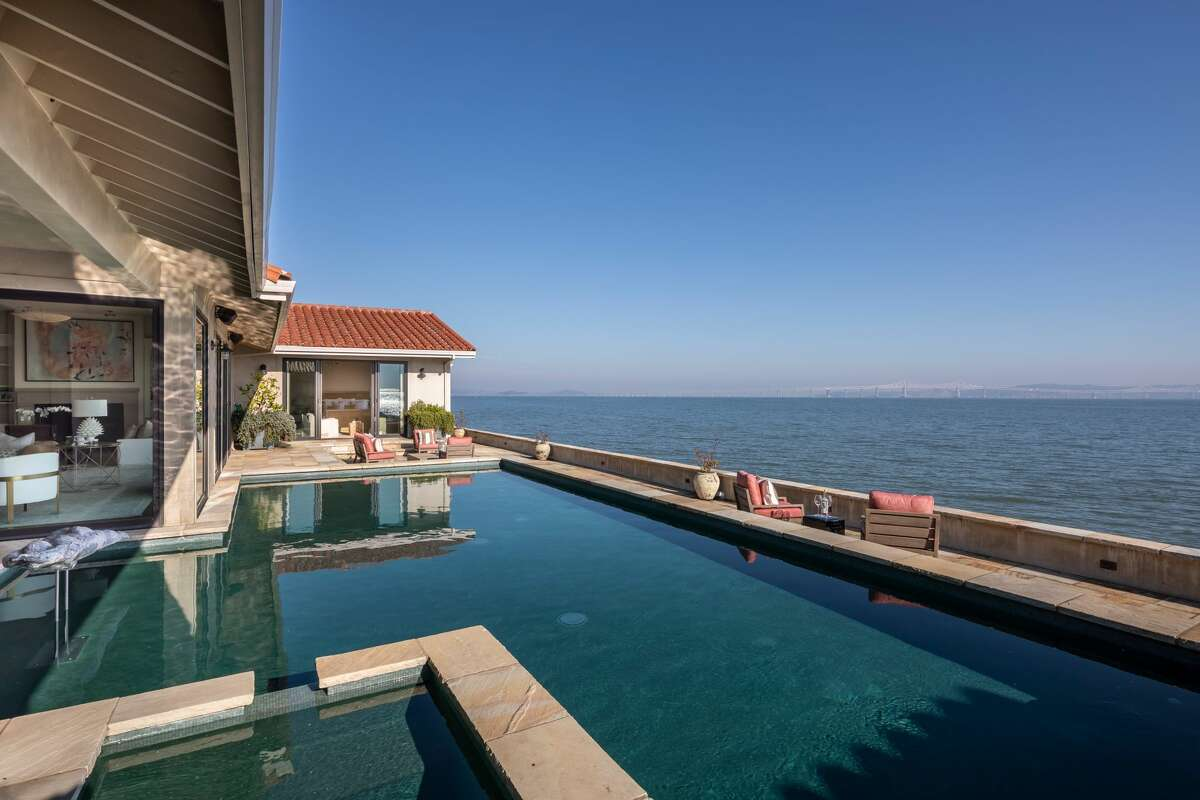 The outdoor patio features a pool and hot tub that overlook the bay. The listing says you can,