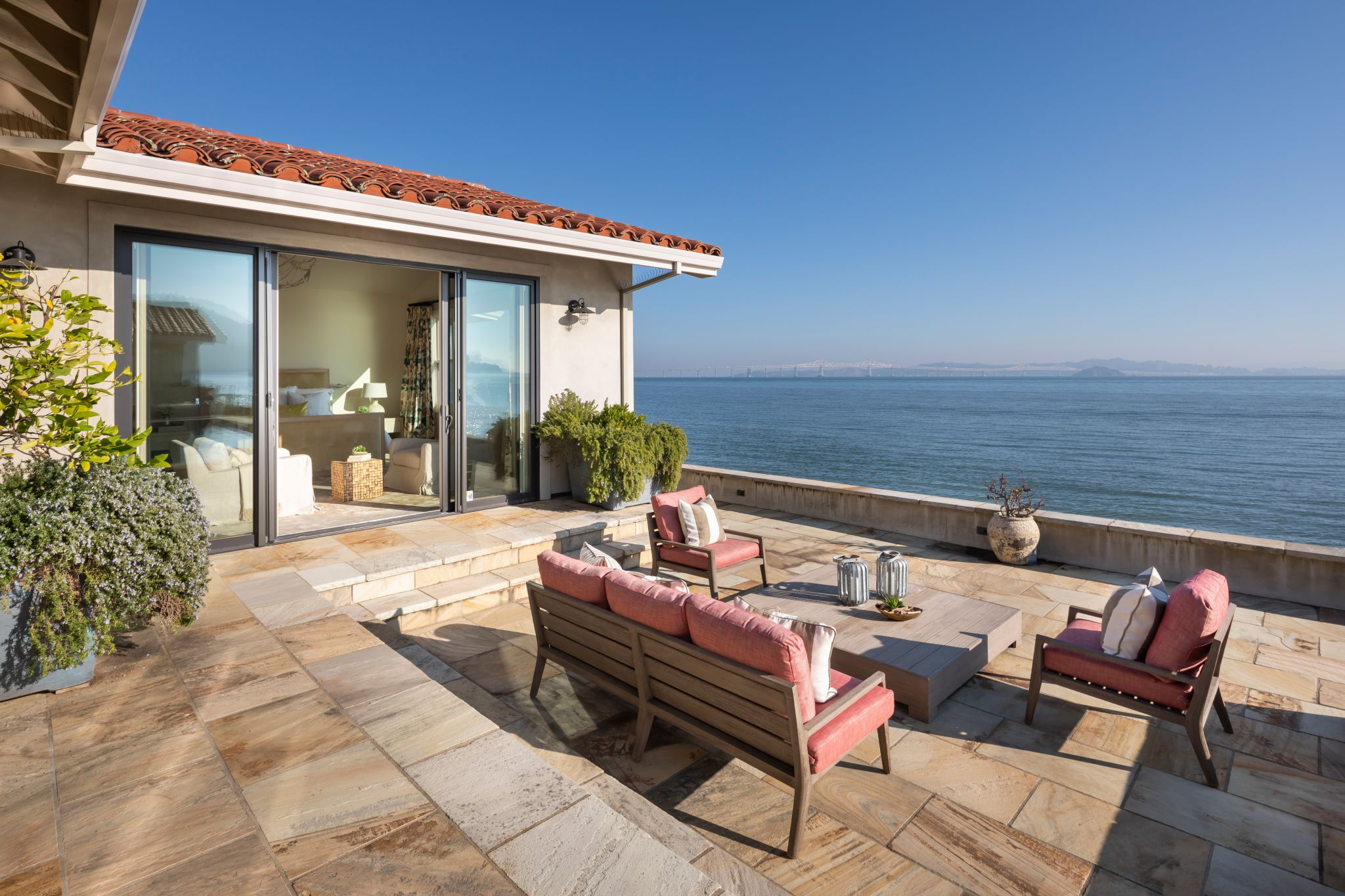 The outdoor patio features a pool and hot tub that overlook the Bay.