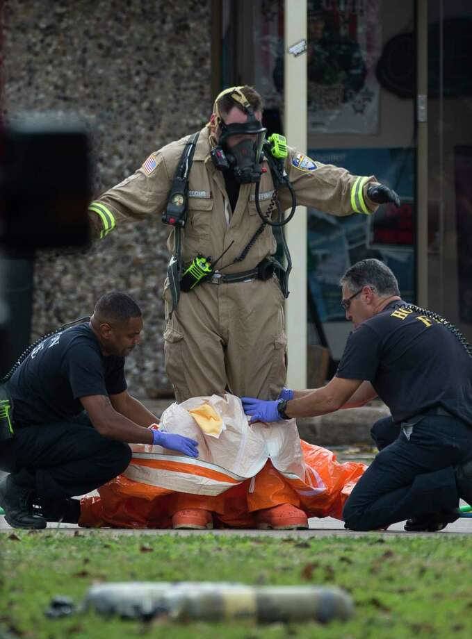 Houston Firefighters help investigators remove the hazmat suit after walked out of the building at 6100 block of West 34th Street on Thursday, Nov. 21, 2019, in Houston. Multiple agencies, including FBI, Houston Police Department, Houston Fire Department and Drug Enforcement Administration officials were working together at the scene. Photo: Yi-Chin Lee, Staff Photographer / © 2019 Houston Chronicle