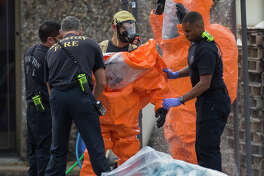 Houston Firefighters help investigators in hazmat suit cleaning up after walked out of the building at 6100 block of West 34th Street on Thursday, Nov. 21, 2019, in Houston. Multiple agencies, including FBI, Houston Police Department, Houston Fire Department and Drug Enforcement Administration officials were working together at the scene.