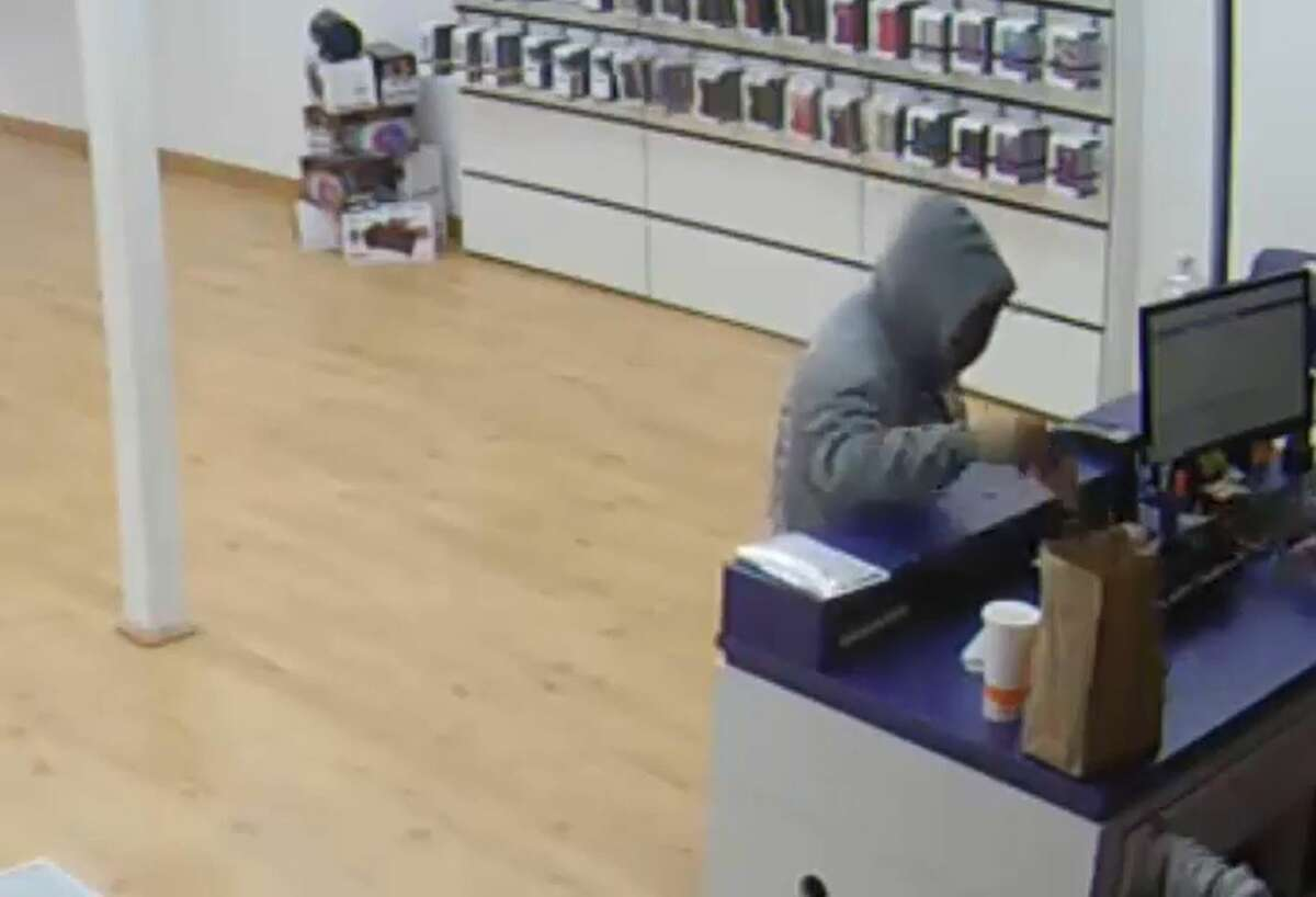 Female suspect takes money from the register.