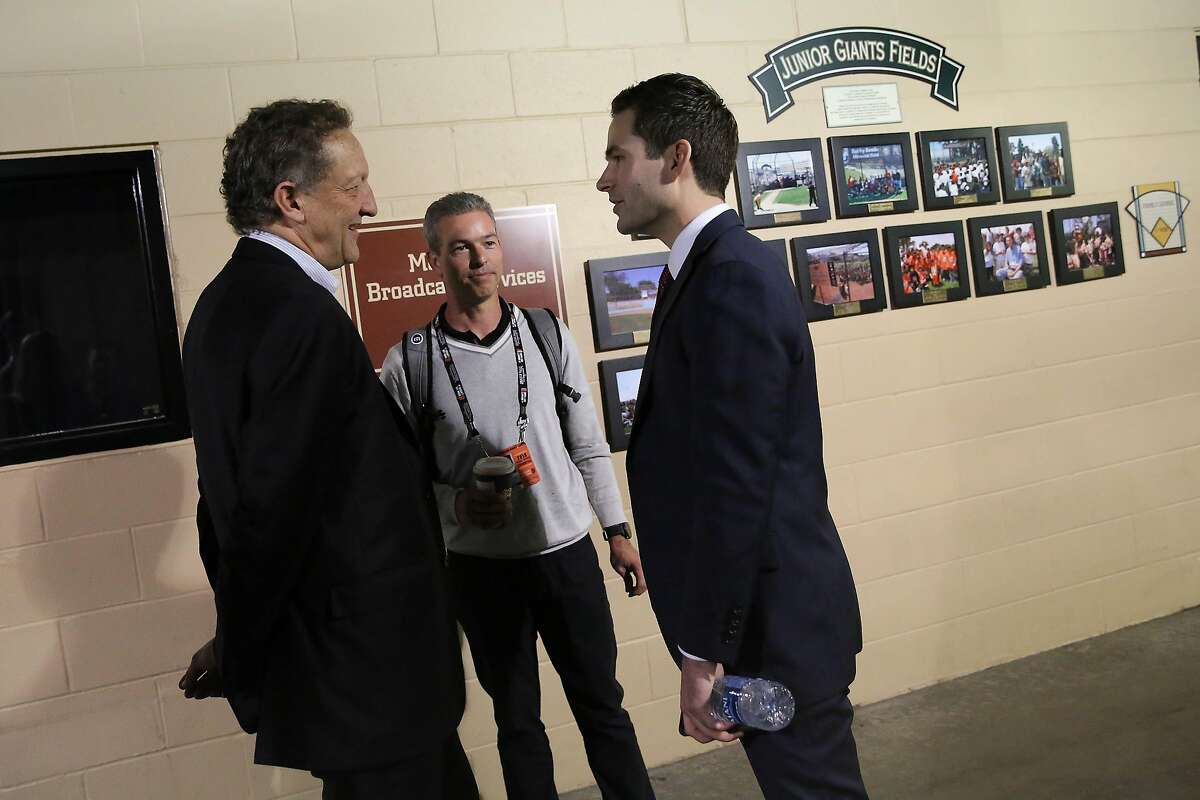 San Francisco Giants' new general manager Scott Harris (right) talks with president and CEO Larry Baer (left) and chairman Rob Dean (center) after speaking at a press conference at Oracle Park on Monday, November 11, 2019 in San Francisco, Calif.