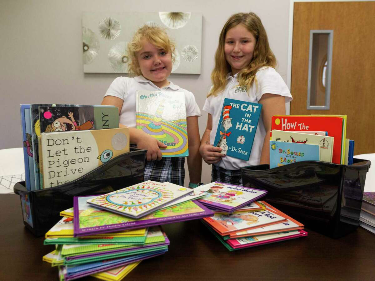 Third graders Katie Harvill, left, and Vanessa Anders pose for a photo with several books students at The Woodlands Christian Academy collected for the Montgomery County Women's Shelter, Wednesday, Nov. 20, 2019, in The Woodlands.