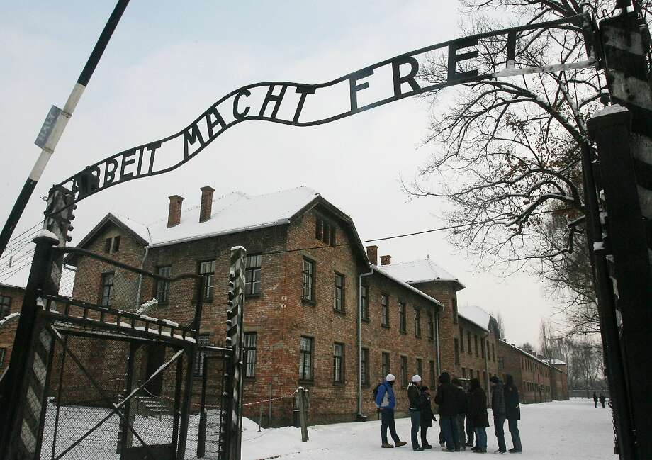 """Tourists pause near the main entrance, with a replica of the inscription """"Arbeit Macht Frei"""" (translated to """"Work Sets You Free"""") over the entranceway to the former Nazi death camp Auschwitz Birkenau, in Oswiecim, southern Poland, Friday, Dec. 18, 2009. Photo: Associated Press"""