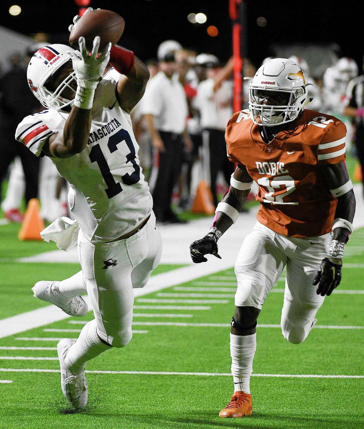 Atascocita wide receiver Landen King (13) catches a pass over Dobie defensive back Darrius Pamplin during the first half of a high school football game, Friday, Oct. 18, 2019, in Pasadena, TX.