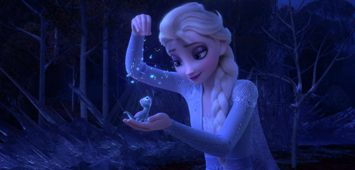 This image released by Disney shows Elsa, voiced by Idina Menzel, sprinkling snowflakes on a salamander named Bruni in a scene from
