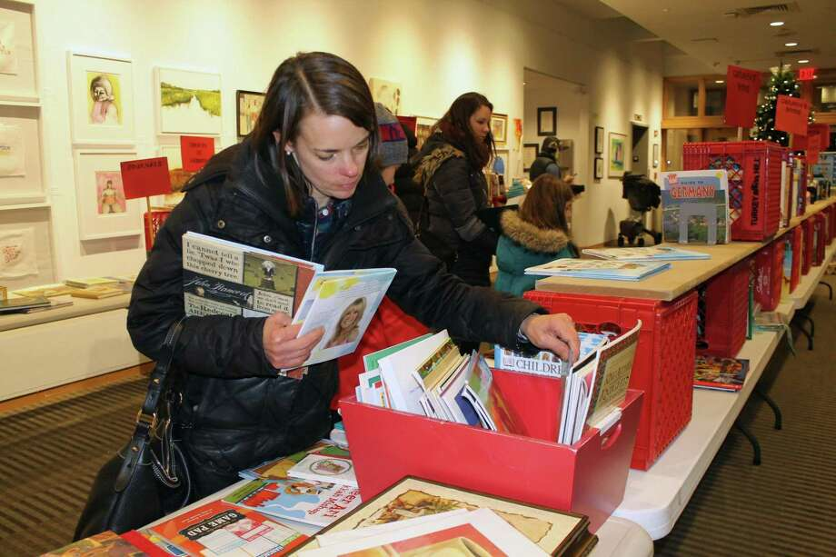 Kim Leonard gets a jump on early holiday shopping at last year's Holiday Book Sale during the Wilton Holiday Stroll. Photo: Janet Crystal / Contributed Photo