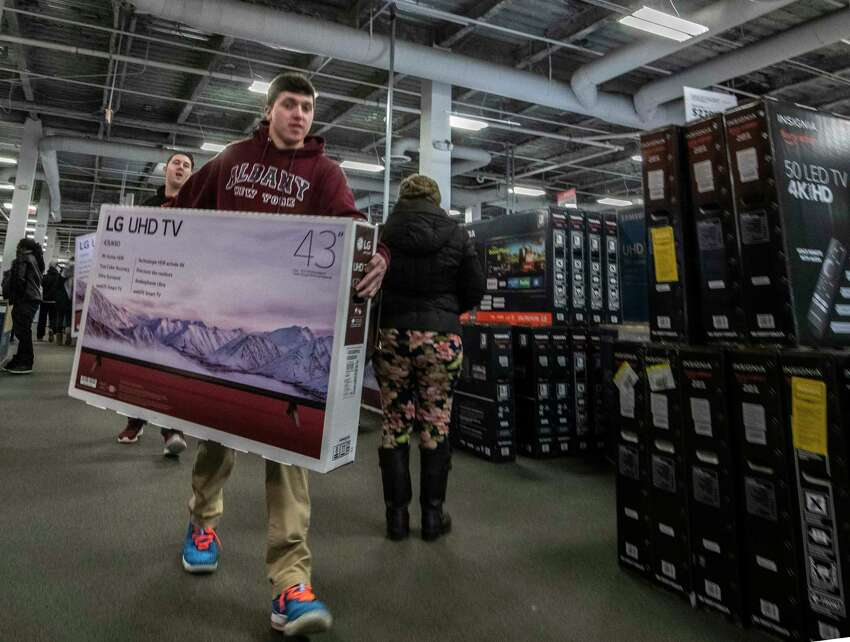 Clyde Sisson, foreground and his pal Ian Classen, background, carry their Black Friday deal TV's from Best Buy at Crossgates Mall Friday Nov. 23, 2018 in Albany, N.Y. (Skip Dickstein/Times Union)