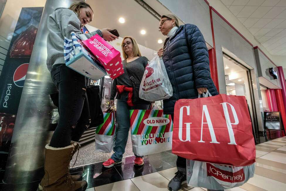 With armloads of gifts and more to go Ally Hogencamp, left, Maria Hogencamp, center and Kelly Lozensky of Hudson plan their next store for shopping at Crossgates Mall on Black Friday Nov. 23, 2018 in Albany, N.Y. (Skip Dickstein/Times Union)