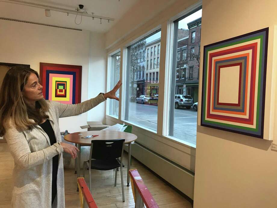 "Michelle Bowen with her painting, ""God Is Love (or How To Have a Conversation),"" part of her ""Huelitic Code"" exhibit at the Arts Center of the Capital Region in Troy. (Photo by Amy Biancolli)"