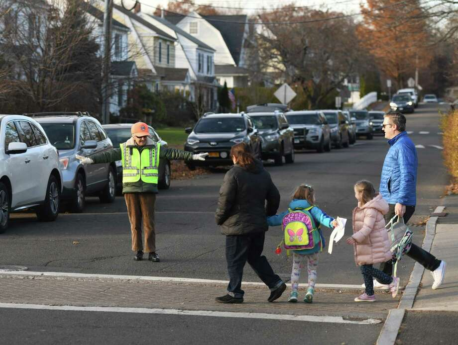 A crossing guard helps students and parents cross a busy intersection during dismissal at Cos Cob School in Greenwich, Conn., on Thursday, Nov. 21, 2019. More crossing guards will be hired this fall. Photo: File / Tyler Sizemore / Hearst Connecticut Media / Greenwich Time