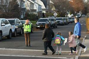 A crossing guard helps students and parents cross a busy intersection during dismissal at Cos Cob School in Greenwich, Conn., on Thursday, Nov. 21, 2019. More crossing guards will be hired this fall.