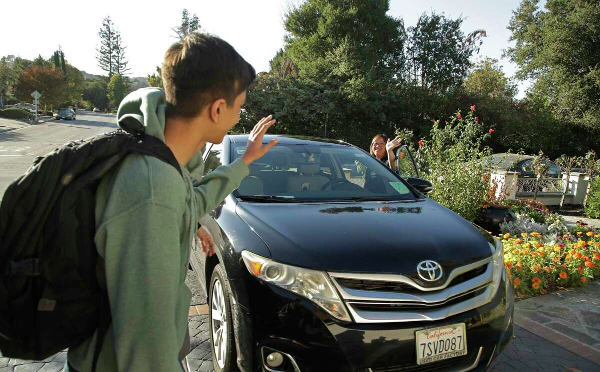 In this photo taken Tuesday, Oct. 29, 2019, Zum driver Stacey Patrick, right, waves goodbye to student Saahas Kohli, left, as he returns home from school in Saratoga, Calif. A handful of ride-hailing companies have surfaced that allow parents to order rides, and in some cases childcare, for children using smartphone apps. The promise is alluring at a time when children are expected to accomplish a dizzying array of extracurricular activities and the boundaries between work and home have blurred. But the companies face hurdles convincing parents that a stranger hired by a ride-hailing company is trustworthy enough to ferry their most precious passengers. (AP Photo/Ben Margot)