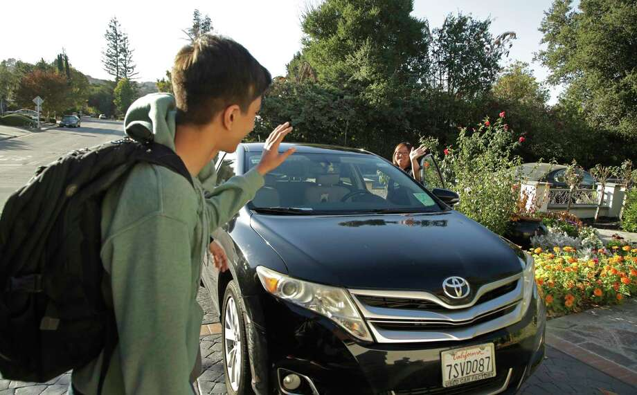 In this photo taken Tuesday, Oct. 29, 2019, Zum driver Stacey Patrick, right, waves goodbye to student Saahas Kohli, left, as he returns home from school in Saratoga, Calif. A handful of ride-hailing companies have surfaced that allow parents to order rides, and in some cases childcare, for children using smartphone apps. The promise is alluring at a time when children are expected to accomplish a dizzying array of extracurricular activities and the boundaries between work and home have blurred. But the companies face hurdles convincing parents that a stranger hired by a ride-hailing company is trustworthy enough to ferry their most precious passengers. (AP Photo/Ben Margot) Photo: Ben Margot / Copyright 2019 The Associated Press. All rights reserved.