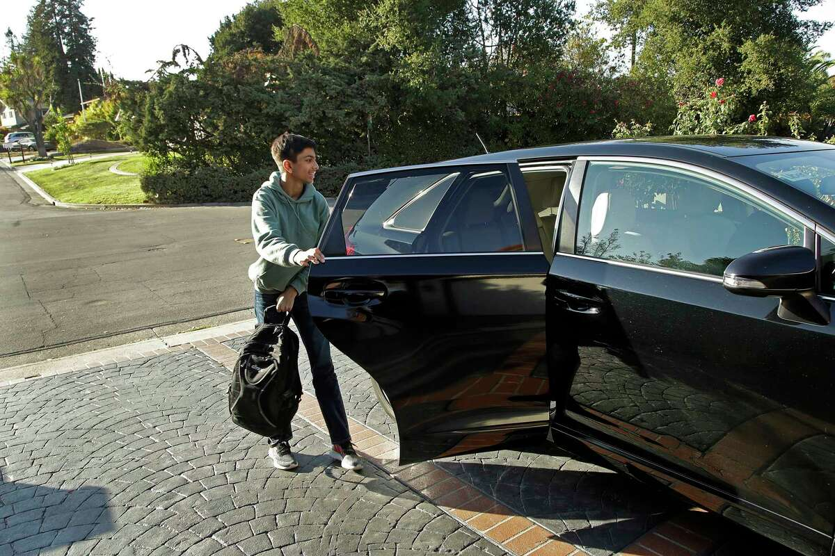In this photo taken Tuesday, Oct. 29, 2019, Saahas Kohli, 14, exits a Zum ride share vehicle at his home in Saratoga, Calif. A handful of ride-hailing companies have surfaced that allow parents to order rides, and in some cases childcare, for children using smartphone apps. The promise is alluring at a time when children are expected to accomplish a dizzying array of extracurricular activities and the boundaries between work and home have blurred. But the companies face hurdles convincing parents that a stranger hired by a ride-hailing company is trustworthy enough to ferry their most precious passengers. (AP Photo/Ben Margot)