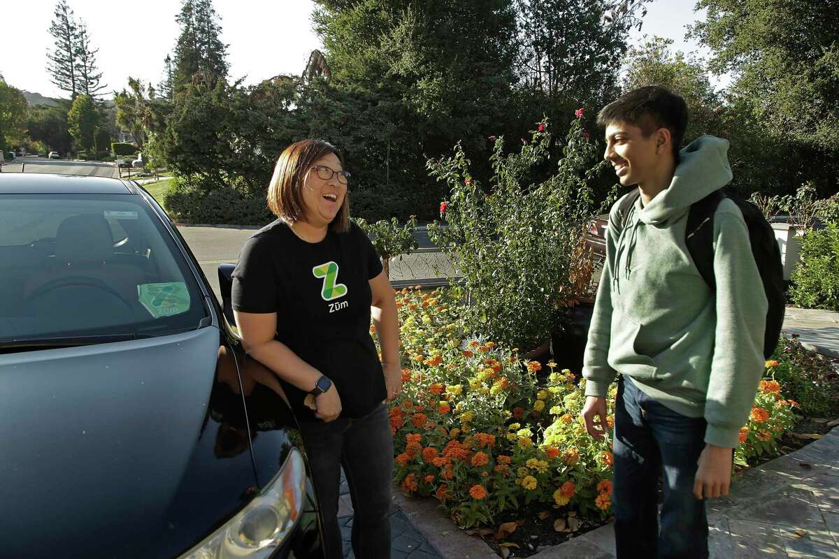 In this photo taken Tuesday, Oct. 29, 2019, Zum driver Stacey Patrick, left, speaks to student Saahas Kohli after driving him home from school in Saratoga, Calif. A handful of ride-hailing companies have surfaced that allow parents to order rides, and in some cases childcare, for children using smartphone apps. The promise is alluring at a time when children are expected to accomplish a dizzying array of extracurricular activities and the boundaries between work and home have blurred. But the companies face hurdles convincing parents that a stranger hired by a ride-hailing company is trustworthy enough to ferry their most precious passengers. (AP Photo/Ben Margot)