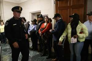 """A U.S. Capitol Police officer walks past a group of veterans with the group, """"Common Defense,"""" who said they were """"standing in vigil in support of impeachment,"""" by the hearing room where the House Intelligence Committee was listening to testimony from former White House national security aide Fiona Hill and David Holmes, a U.S. diplomat in Ukraine, on Capitol Hill in Washington, Thursday, Nov. 21, 2019, during a public impeachment hearing of President Donald Trump's efforts to tie U.S. aid for Ukraine to investigations of his political opponents. (AP Photo/Jacquelyn Martin)"""