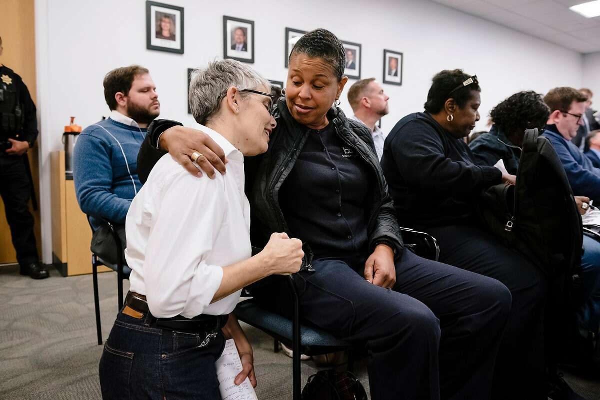 BART station agent Suzanne Gamble, left, gets a hug and advice from South Hayward station agent and station agent representative Stephanie Barnes during a BART meeting in Oakland, California, Monday, November 21, 2019.
