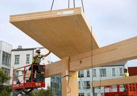 A cross-laminated timber floor panel is lowered into position for installation at an office building construction project in San Francisco, Calif. on Friday, Nov. 15, 2019. The One De Haro project is the first in the city to utilize the cross-laminated timber process.
