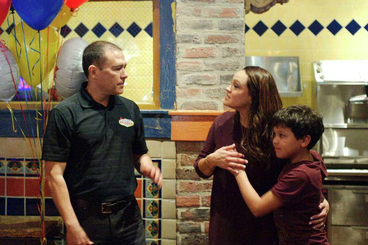 Charity Burkland receives a hug from her son Nate as she chats with Gringo's Mexican Kitchen president and founder Russell Ybarra during lunch where proceeds from the day benefited the Burkland family.