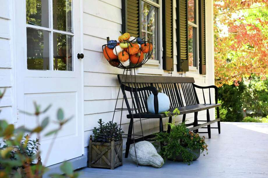 The front porch of Jo Oliver's home is dressed for the season. Over the years she has bought hanging metal baskets from Terrain to hold gourds and pumpkins. Photo: Katherine Frey, The Washington Post / The Washington Post / The Washington Post