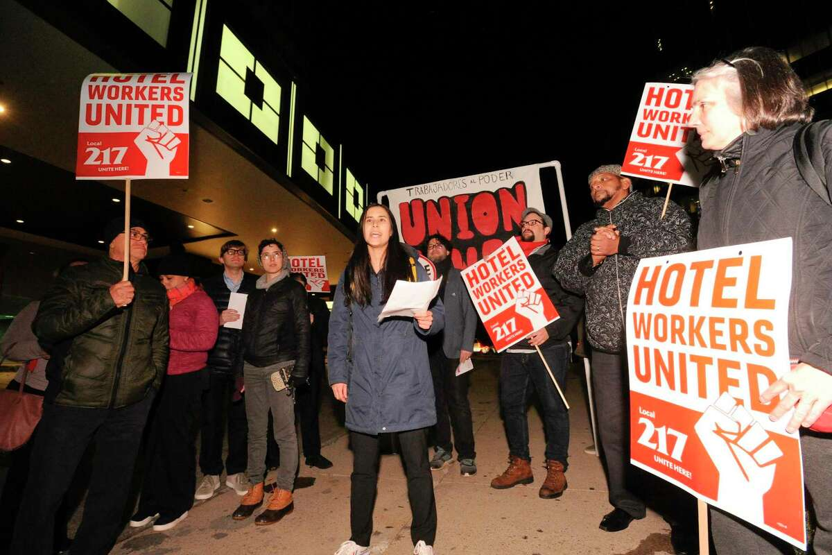 Talia Stender, center, with the Yale Law School Worker and Immigrant Rights Advocacy Clinic speaks as hotel workers from the Stamford Sheraton protest outside the hotel on Nov. 21, 2019 in Stamford, Conn. The Stamford Sheraton announced April 13, 2020 that it was cutting about 100 positions amid the coronavirus crisis.