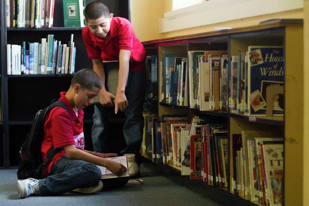 In this file photo, Hogg Middle School 8th graders Tony Vasquez, sitting, and Jesse Gonzalez look through books in the school library. Only a third of HISD schools have a certified librarian on staff.