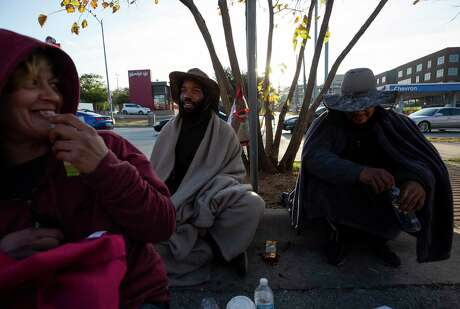 Therron Hines, center, and O.D. Benjamin, right, hang out on the sidewalk of Interstate 35 Frontage Road Monday, Nov. 4, 2019, in Austin.