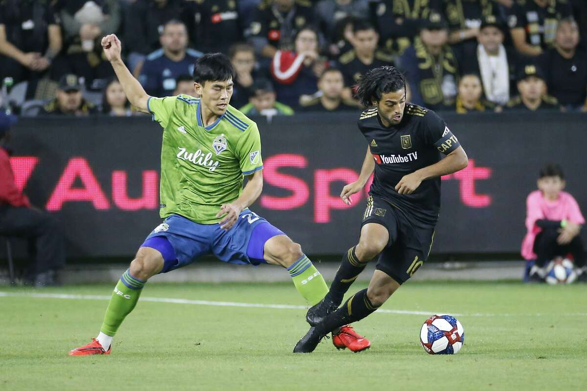 Seattle Sounders defender Kim Kee-hee (20) vies with Los Angeles FC forward Carlos Vela (10) during the first half of the MLS soccer Western Conference final, Tuesday, Oct. 29, 2019, in Los Angeles. (AP Photo/Ringo H.W. Chiu)