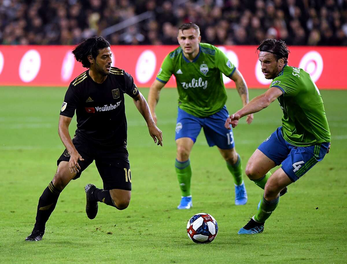 LOS ANGELES, CALIFORNIA - OCTOBER 29: Carlos Vela #10 of Los Angeles FC dribbles the ball away from Gustav Svensson #4 and Jordan Morris #13 of Seattle Sounders during the first half during the Western Conference finals at Banc of California Stadium on October 29, 2019 in Los Angeles, California. (Photo by Harry How/Getty Images)