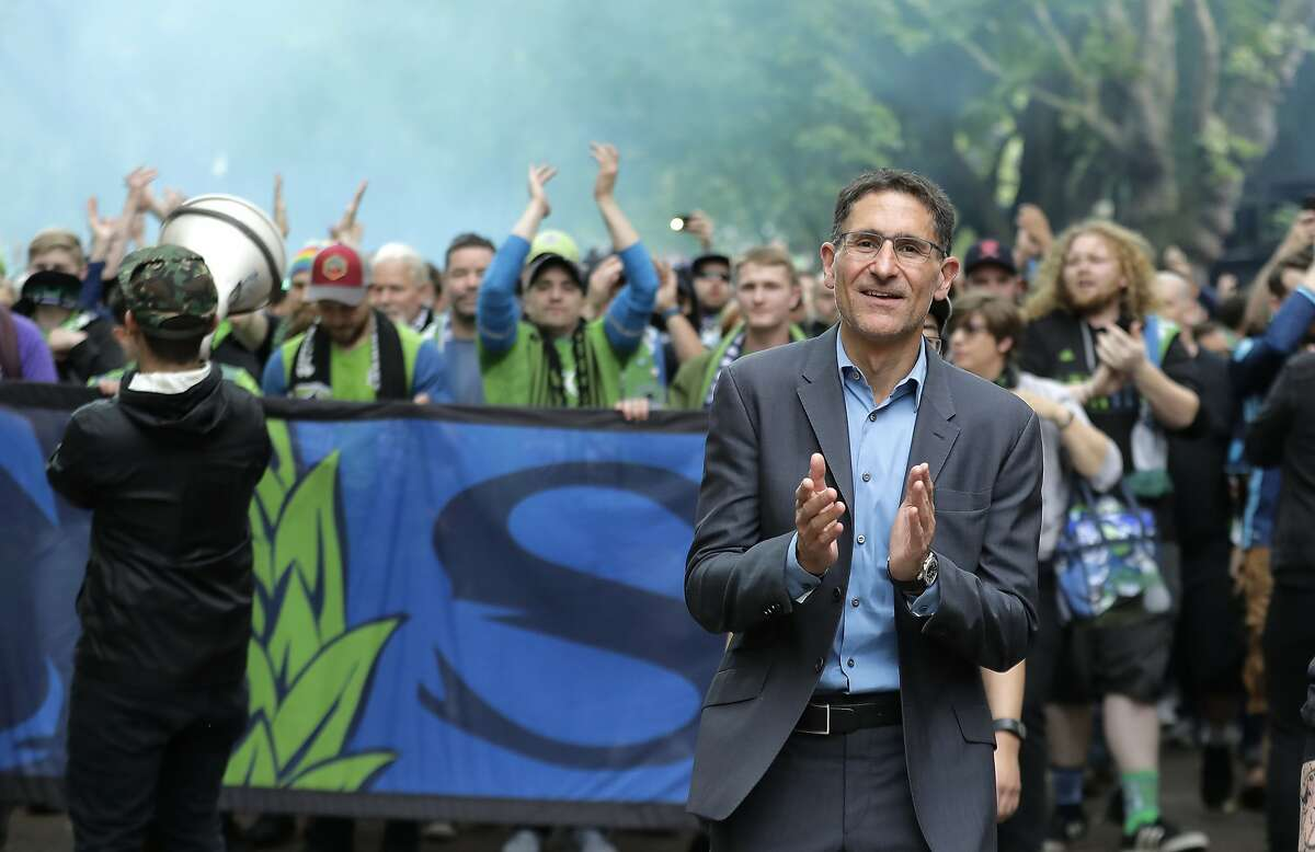 FILE - In this June 30, 2018, file photo, Seattle Sounders owner Adrian Hanauer, right, takes part in the traditional March to the Match before an MLS soccer match in Seattle. Seattle will host the MLS Cup soccer match Sunday, Nov. 10, 2019, as the Sounders face Toronto FC at CenturyLink Field. (AP Photo/Ted S. Warren, File)