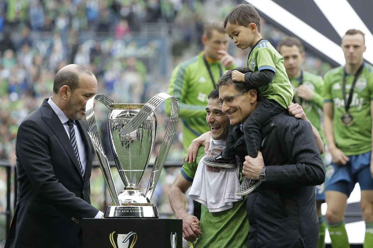 Seattle Sounders captain Nicolas Lodeiro, center, is hugged by team owner Adrian Hanauer as MLS Commissioner Don Garber, left, prepares to hand over the MLS Cup trophy Sunday, Nov. 10, 2019, after the Sounders beat Toronto FC in the MLS Cup championship soccer match in Seattle. (AP Photo/Ted S. Warren)
