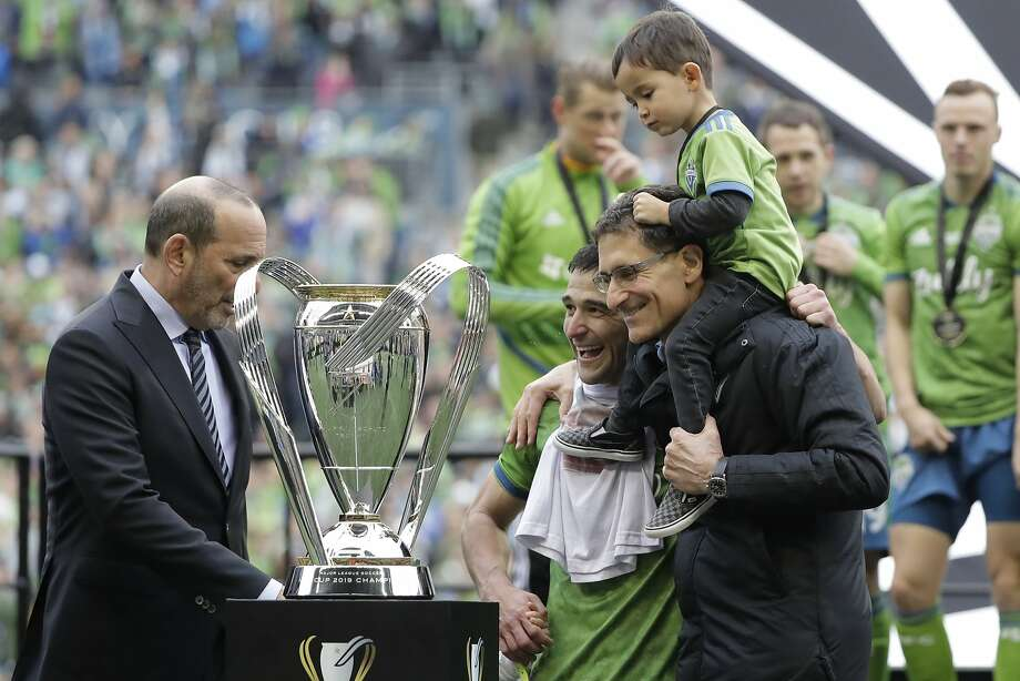 Seattle Sounders captain Nicolas Lodeiro, center, is hugged by team owner Adrian Hanauer as MLS Commissioner Don Garber, left, prepares to hand over the MLS Cup trophy Sunday, Nov. 10, 2019, after the Sounders beat Toronto FC in the MLS Cup championship soccer match in Seattle. (AP Photo/Ted S. Warren) Photo: Ted S. Warren, Associated Press