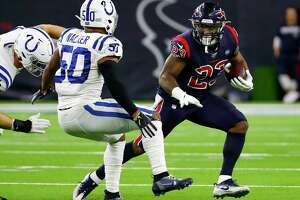 Houston Texans running back Carlos Hyde (23) tries to run around Indianapolis Colts middle linebacker Anthony Walker (50) during the first quarter of an NFL football game at NRG Stadium on Thursday, Nov. 21, 2019, in Houston.