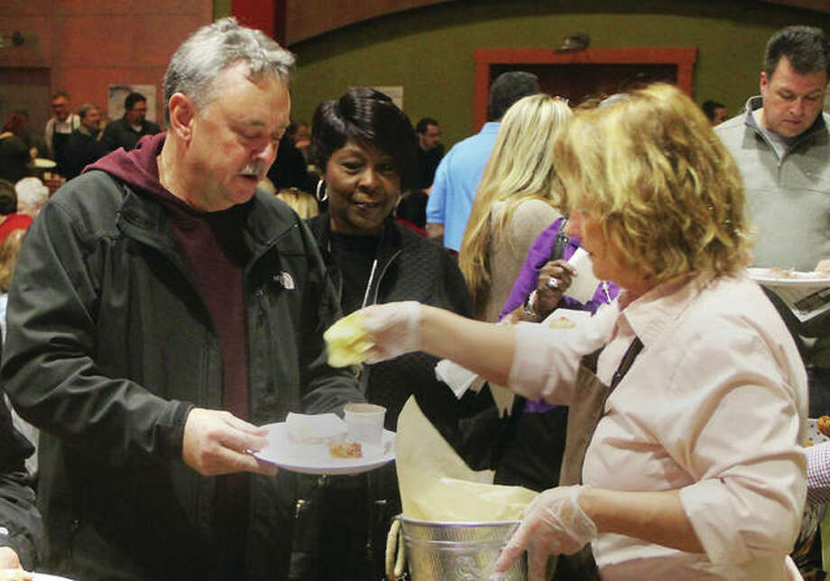Jeff Norton, of Bunker Hill, gets chips from the Brown Bag Bistro at Taste of Downtown 2019, a fundraiser for Alton Main Street. About 400 people came out for the event, which included chances to taste samples from more than a dozen area restaurants, music and prizes.