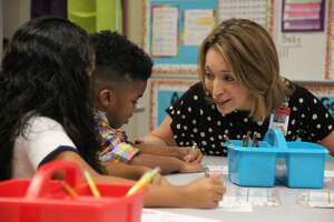 Judson Superintendent Jeanette Ball talks with two elementary school children Aug. 20 on the first day of school.
