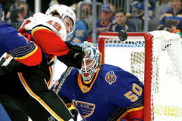 The Flames' Matthew Tkachuk (19) and Blues goaltender Jordan Binnington watch the puck in the air in the third period of Thursday night's game in St. Louis. The Blues won 5-0.