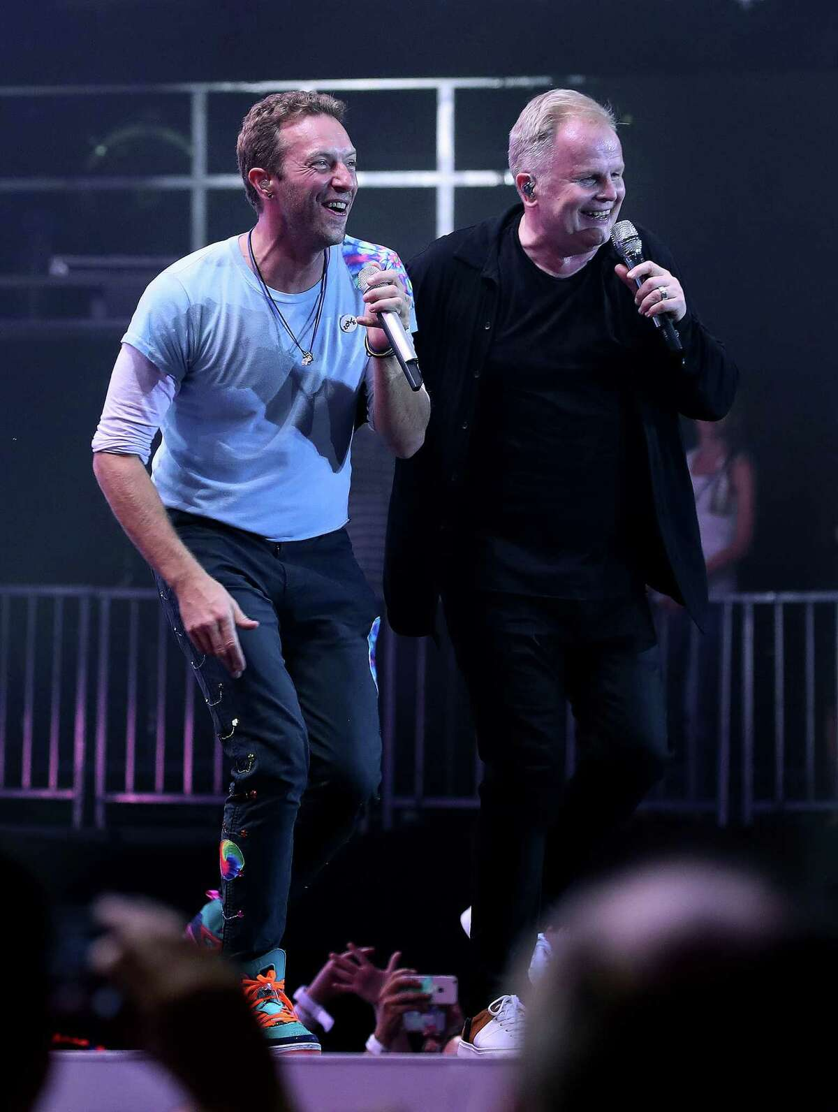 Chris Martin (L) of Coldplay and German singer Herbert Groenemeyer (R) perform on stage during the Global Citizen Festival G20 benefit concert at the Barclaycard Arena in Hamburg, northern Germany on July 6, 2017 on the eve of the G20 summit. Leaders of the world's top economies will gather from July 7 to 8, 2017 in Germany for likely the stormiest G20 summit in years, with disagreements ranging from wars to climate change and global trade. / AFP PHOTO / RONNY HARTMANNRONNY HARTMANN/AFP/Getty Images