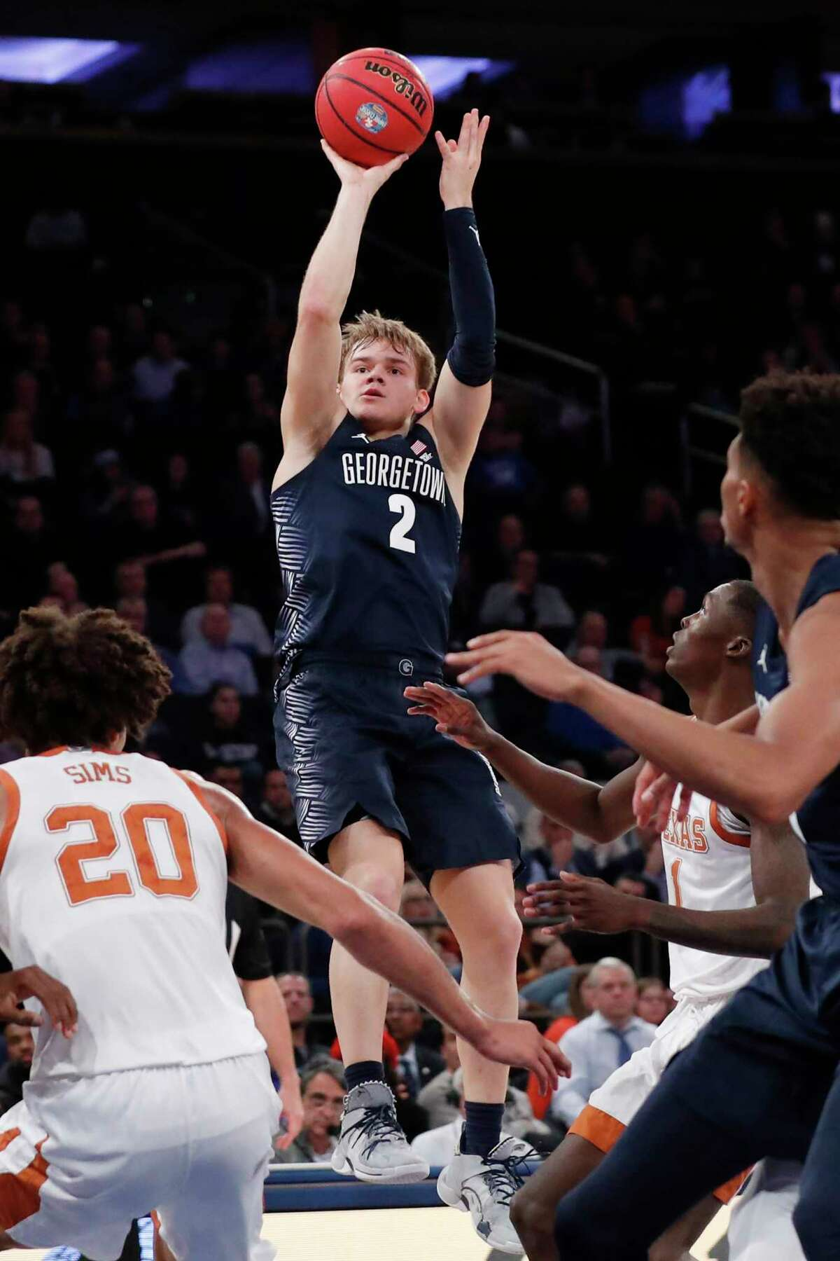 Georgetown guard Mac McClung (2) goes up for a shot as Texas forward Jericho Sims (20) looks on, below left, during the second half of the first round of the 2K Empire Classic NCAA college basketball tournament, Thursday, Nov. 21, 2019, in New York. McClung was the high scorer as Georgetown defeated Texas 82-66. (AP Photo/Kathy Willens)