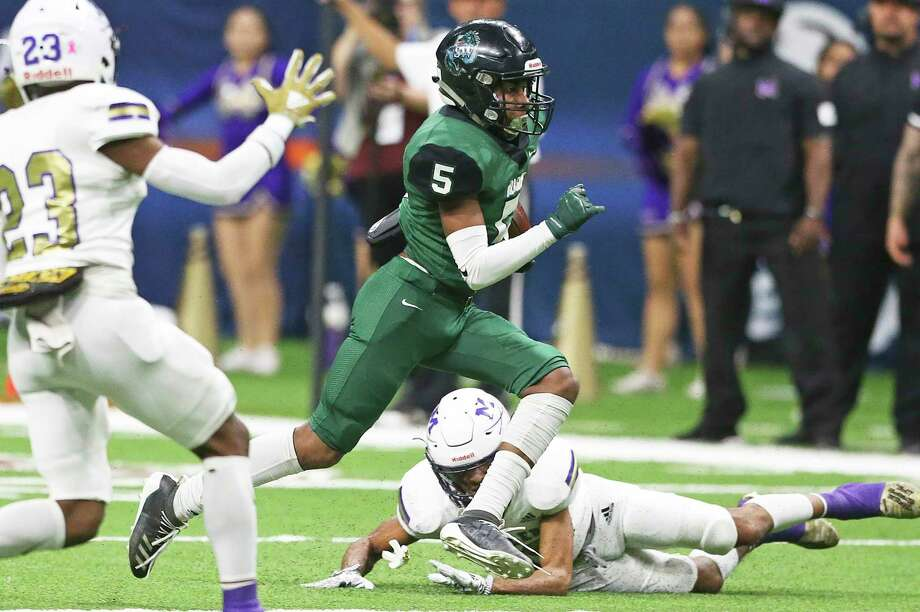 Dragons running back Andre Mitchell gets between defenders on a first quarter run as Southwest plays Corpus Christi Miller in the second round of high school football playoffs at the Alamodome on Nov.21, 2019. Photo: Tom Reel, San Antonio Express-News / Staff Photographer / **MANDATORY CREDIT FOR PHOTOG AND  SAN ANTONIO EXPRESS-NEWS/NO SALES/MAGS OUT/TV
