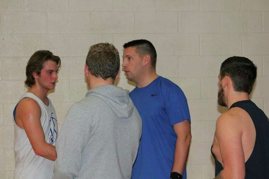 Chppewa Hills coach Zach Ingles (second from right) talks to his team after a practice on Wednesday. (Pioneer photo/John Raffel)