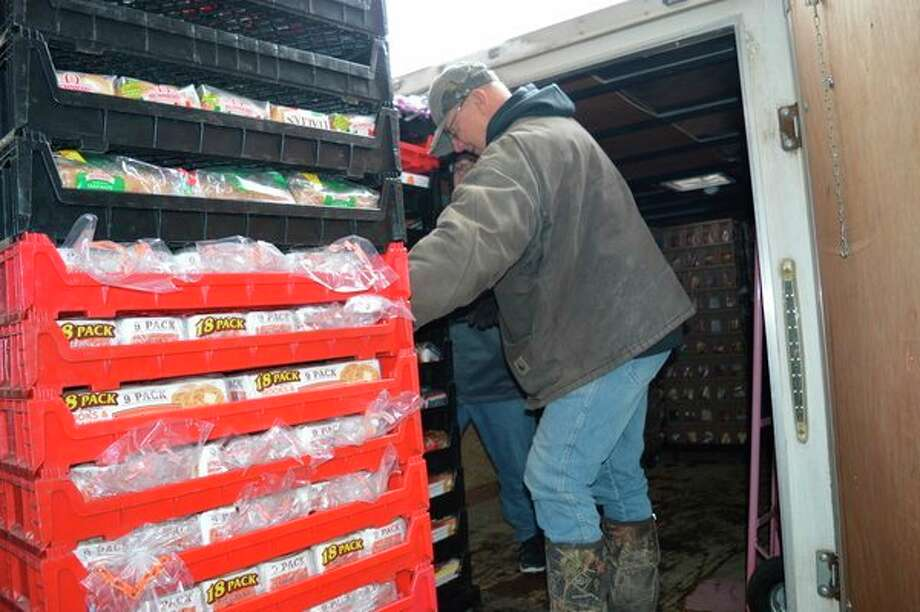 A Hidden Harvest staff member loads bread onto a truck to take to local non-profit organizations. (Emilly Davis/For the Daily News)