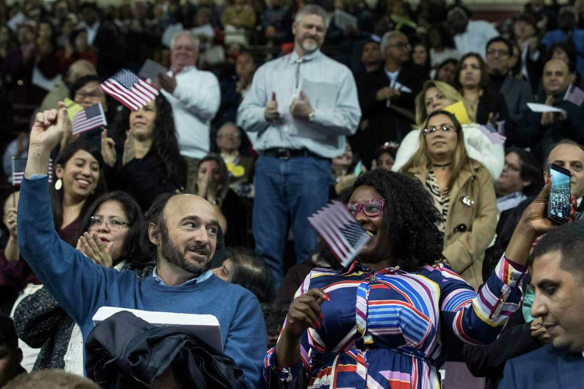 Juan L. Fernandez, left, from Portugal, and Chioma Anyanwu, from Nigeria, celebrate after taking the oath of allegiance during a naturalization ceremony for more than 2,500 new Americans at the M.O. Campbell Educational Center on Wednesday, Nov. 13, 2019, in Houston. As the state gears up for what could be its most important election in decades, thousands of would-be voters are caught in limbo, stuck in a deep and growing backlog of immigrants applying for U.S. citizenship. While the Trump administration says it is devoting resources to cut down on the backlog, and attorneys in Houston say immigrations officials do appear to be making an effort to get more applications through.