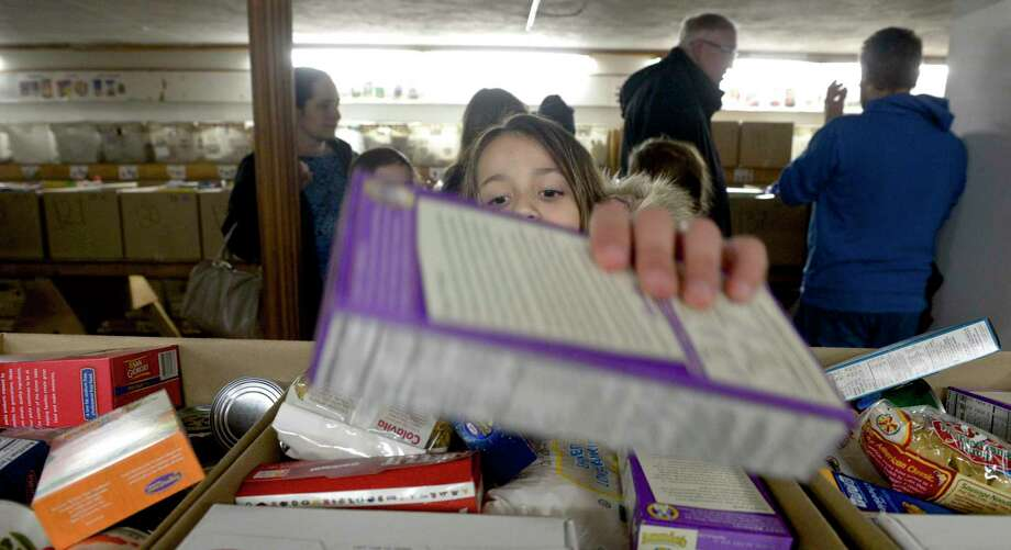 Amber Luque, 8, of Bethel, volunteered at Brotherhood in Action, a Bethel based food pantry, to pack boxes of food to be delivered to families in need. The pantry expects to give food to 140 families. Wednesday night, November 20, 2019, in Bethel, Conn. Photo: H John Voorhees III / Hearst Connecticut Media / The News-Times