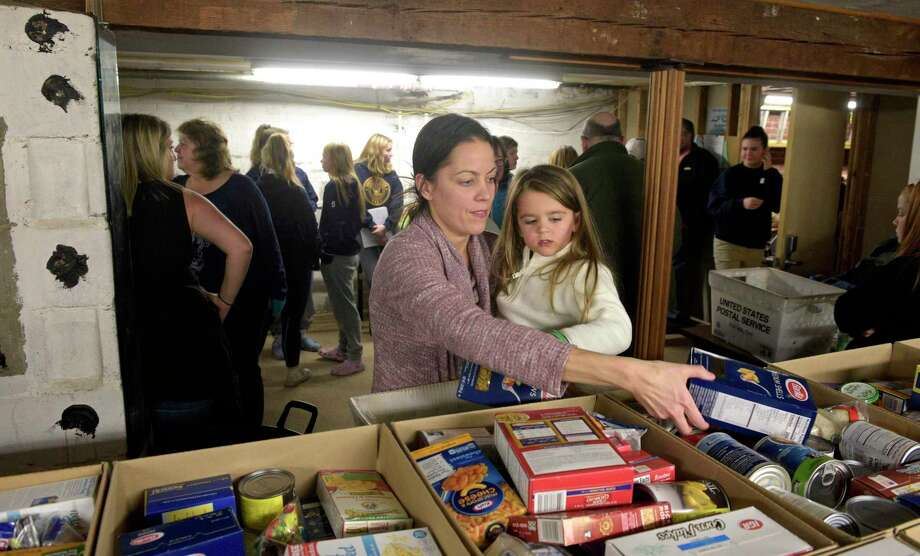 Kim Rissolo, of Bethel, and her daughter Chloe, 3, volunteered at Brotherhood in Action, a Bethel based food pantry, to pack boxes of food to be delivered to families in need. The pantry expects to give food to 140 families. Wednesday night, November 20, 2019, in Bethel, Conn. Photo: H John Voorhees III / Hearst Connecticut Media / The News-Times